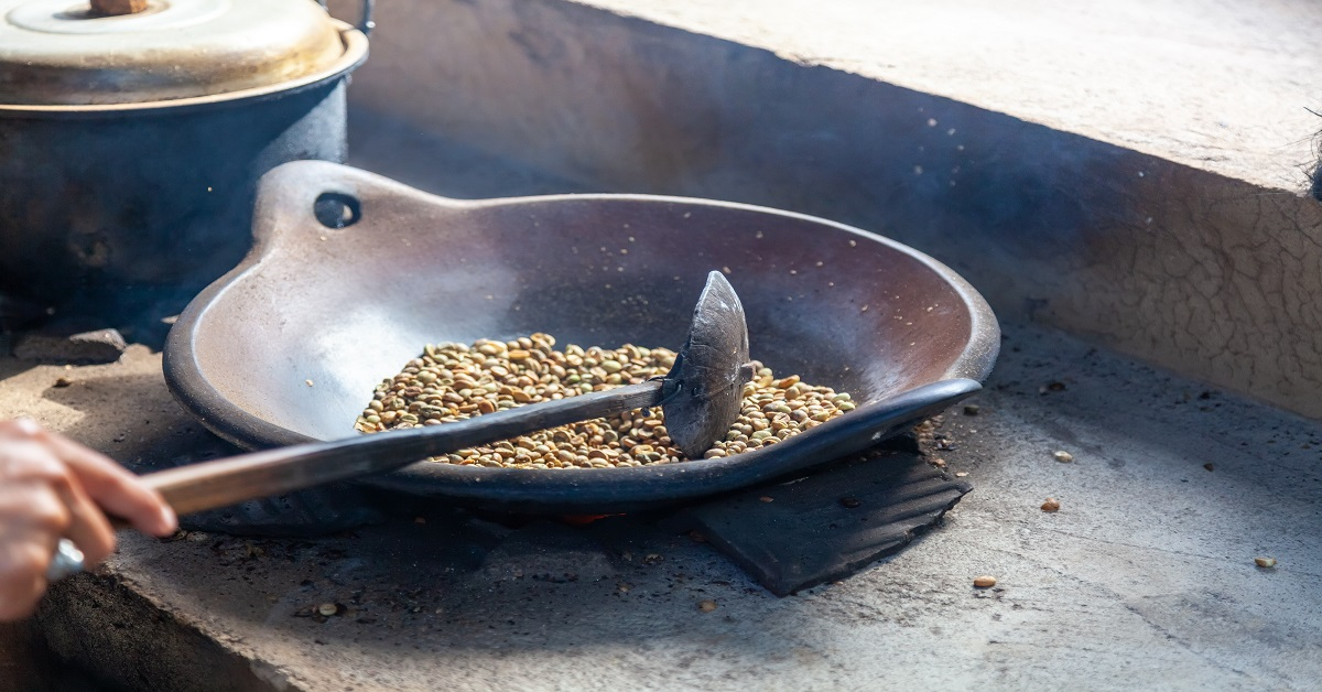 Indonesia traditional roasting fresh coffee beans in a skillet